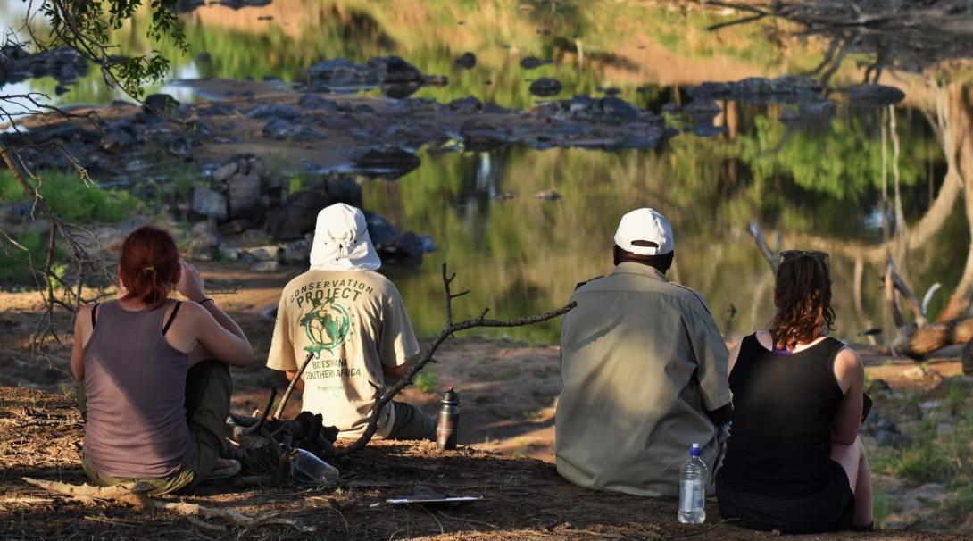 Voluntarios medioambientales en Botsuana descansando junto a un lago.